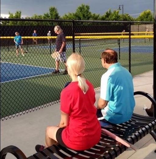 A man and woman watching a pickleball game from a bench under a bright yellow umbrella.